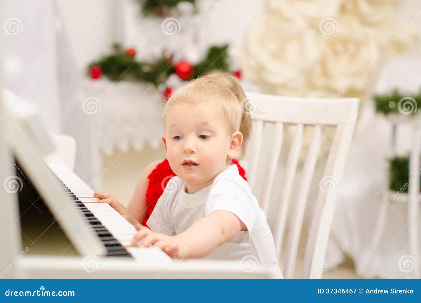 Pojke och flicka som spelar på det vita pianot