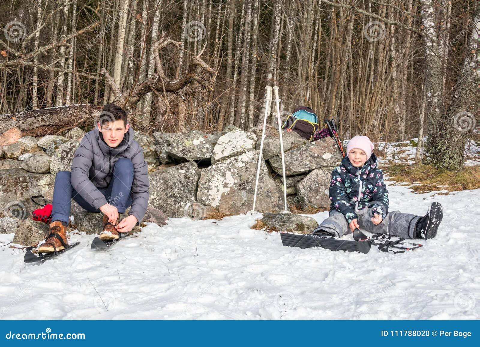 Pojke- och flickasammanträde i snön som sätter på deras, skidar mot en stenvägg