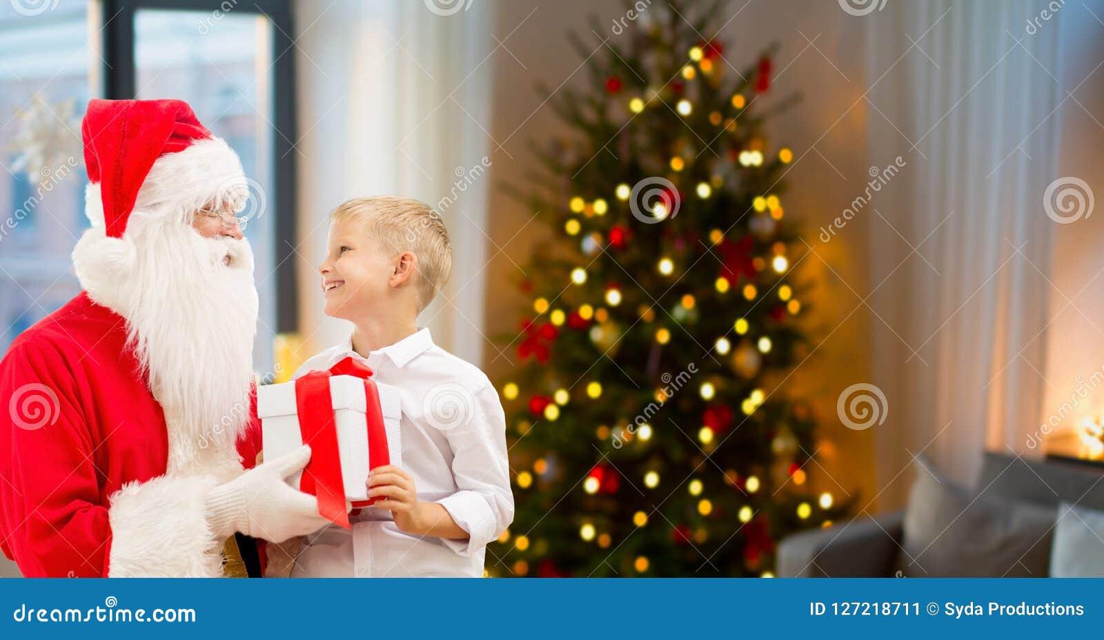 Pojke och santa med julgåvor hemma