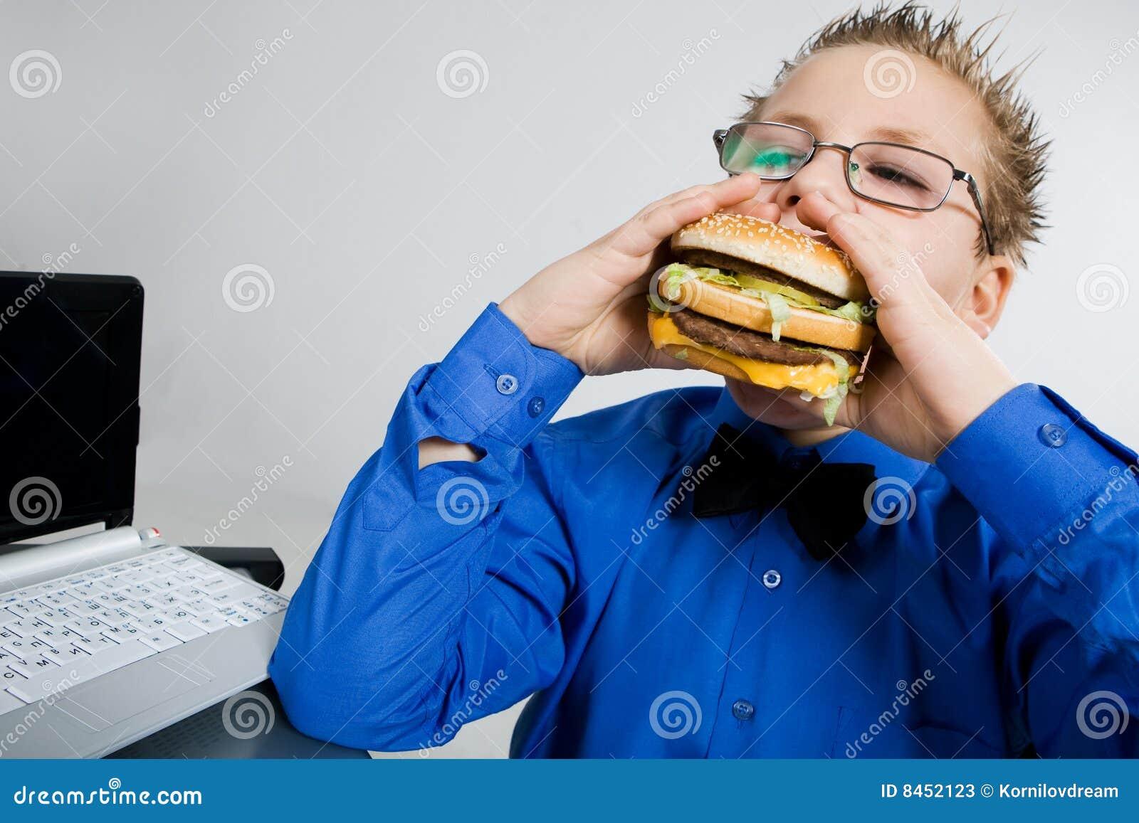 Pojke som äter hamburgareskolabarn