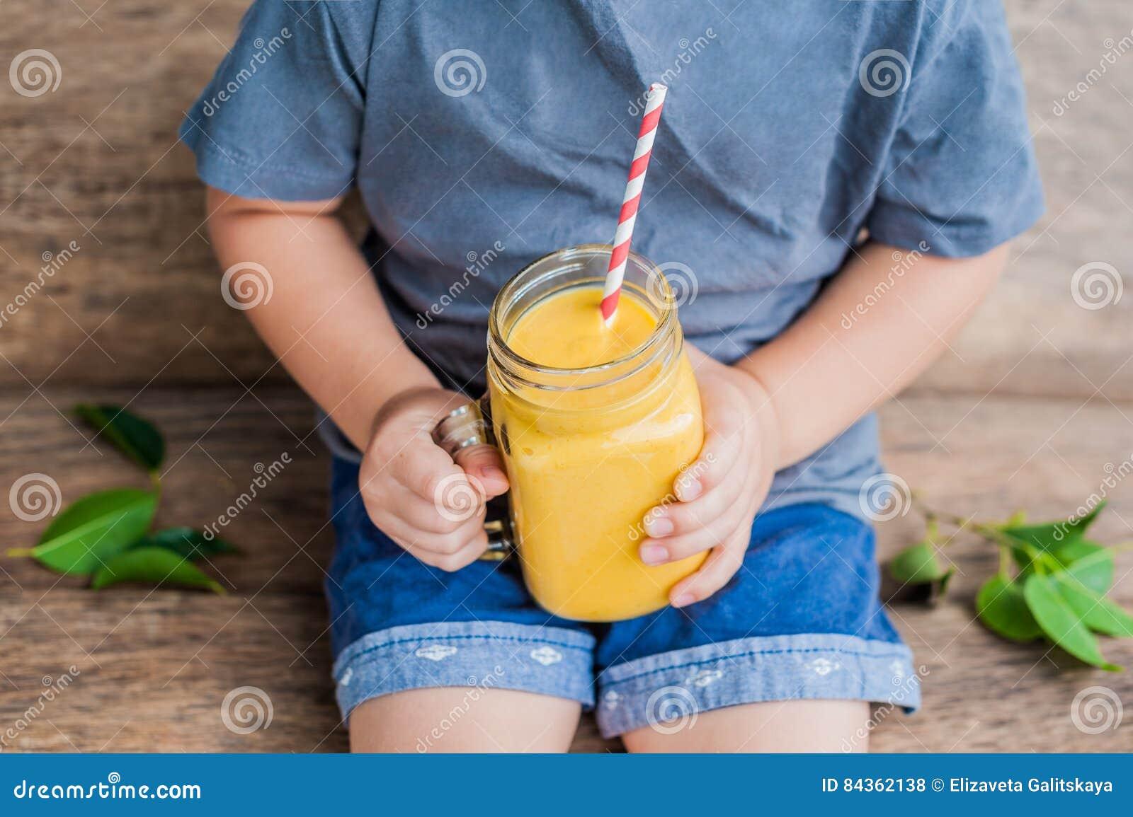 Pojke som dricker den saftiga smoothien från mango i den glass murarekruset med randigt rött sugrör på gammal träbakgrund Sunt li