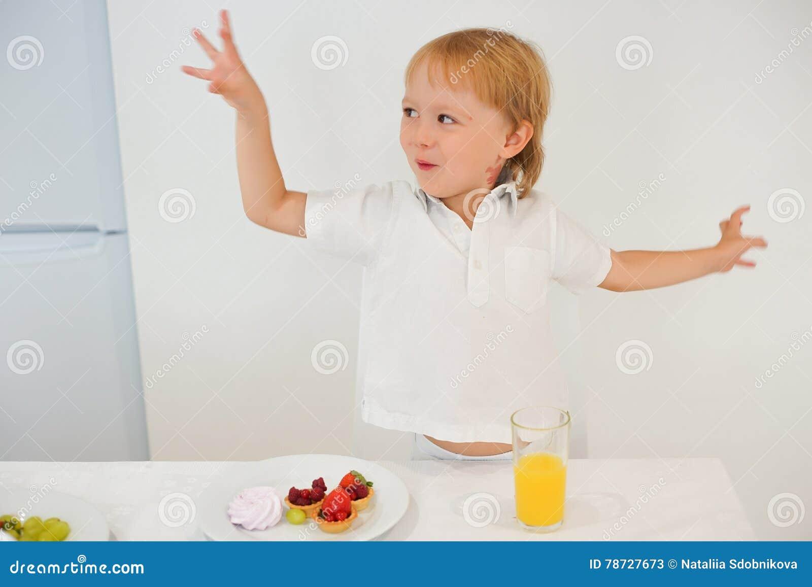 Pojke som förbereder frukosten i vitt kök