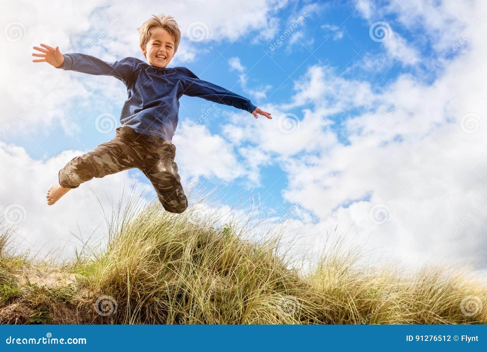 Pojke som hoppar och hoppar över sanddyn på strandsemester