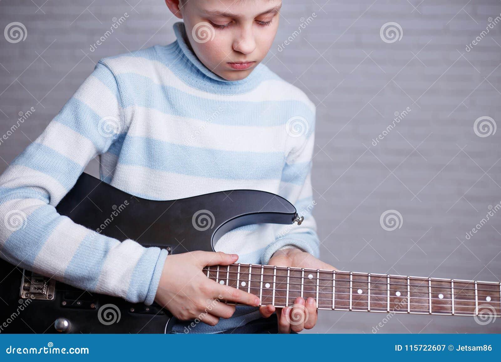 Pojke som lär att spela en elektrisk gitarr Musik, hobby och leisur