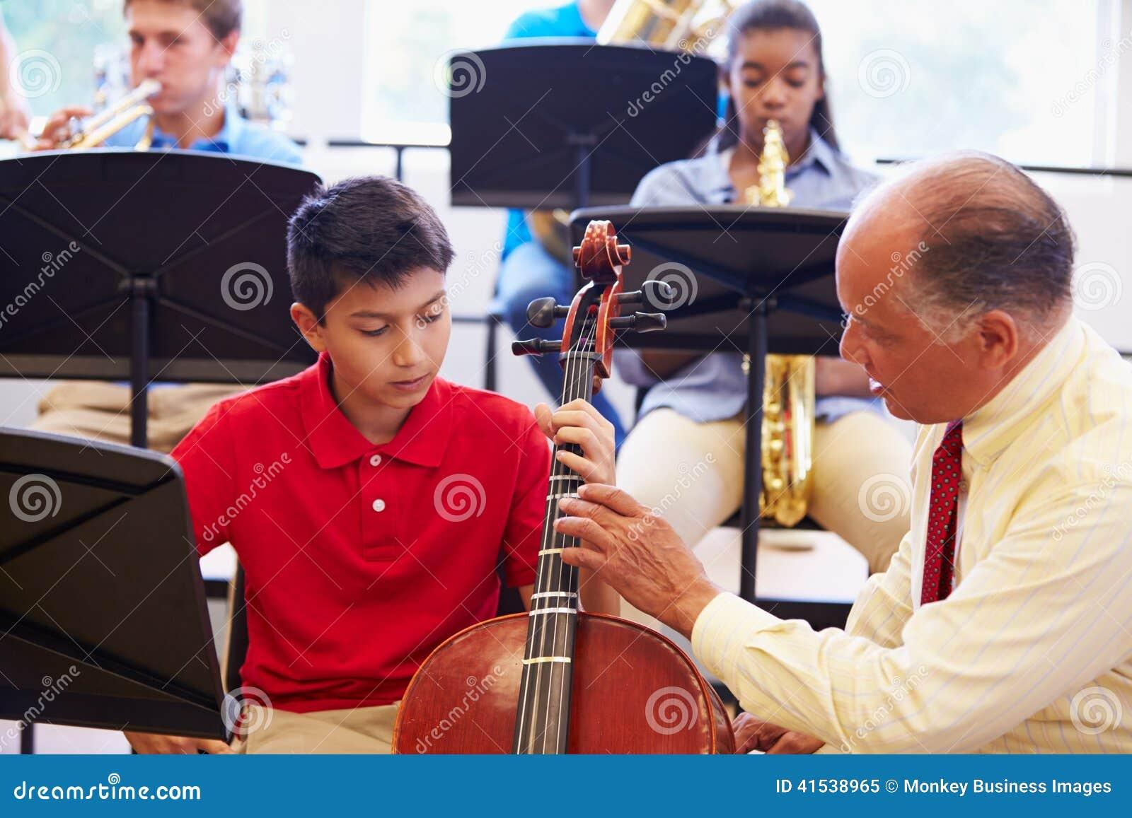 Pojke som lär att spela violoncellen i högstadiumorkester