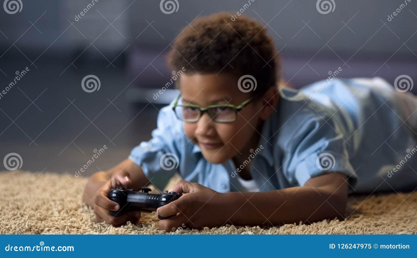 Pojke som ser skärmen, medan spela videospelet, vård- skada, stillasittande livsstil