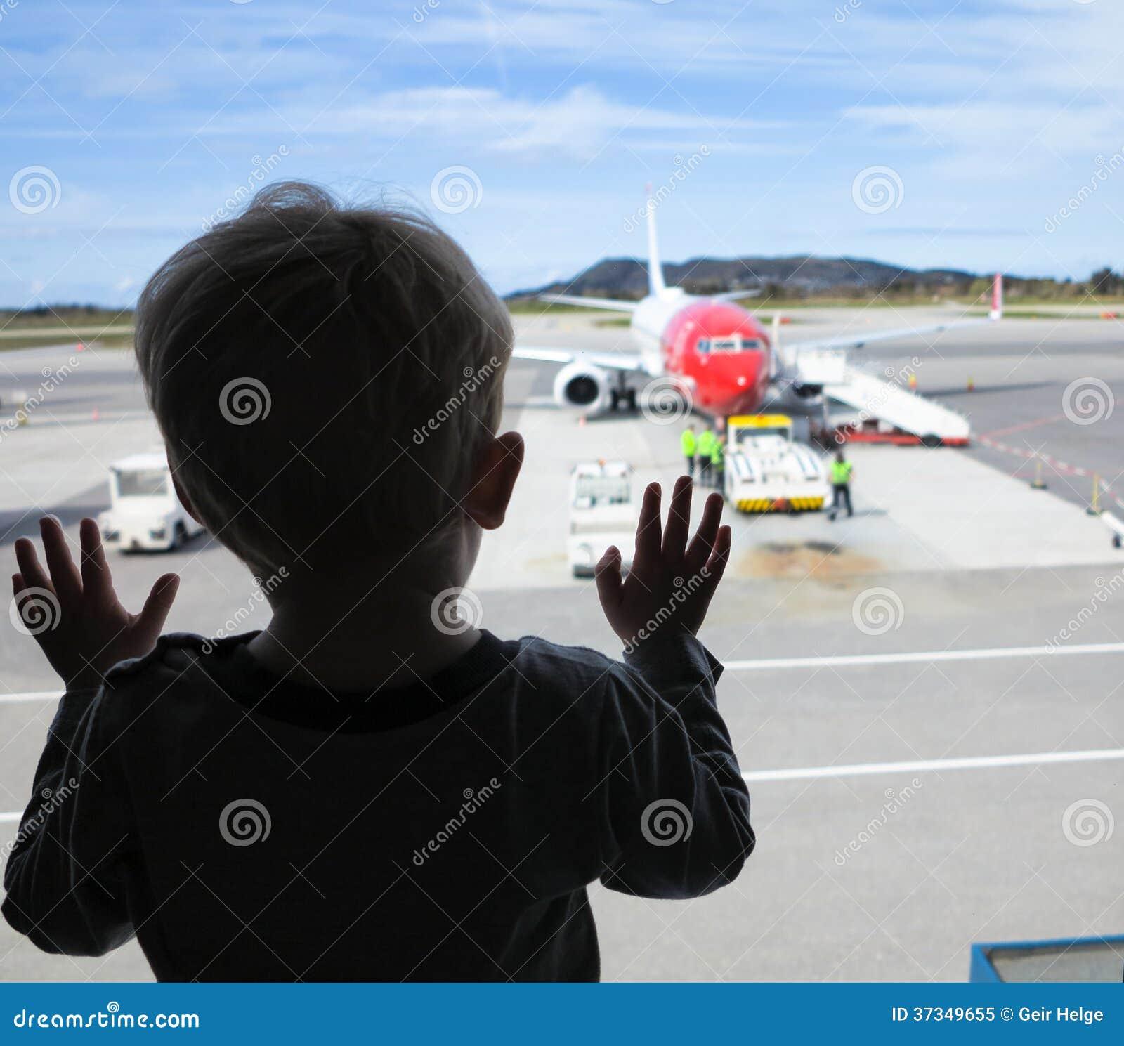 Pojke som ser till och med ett fönster på flygplatsen
