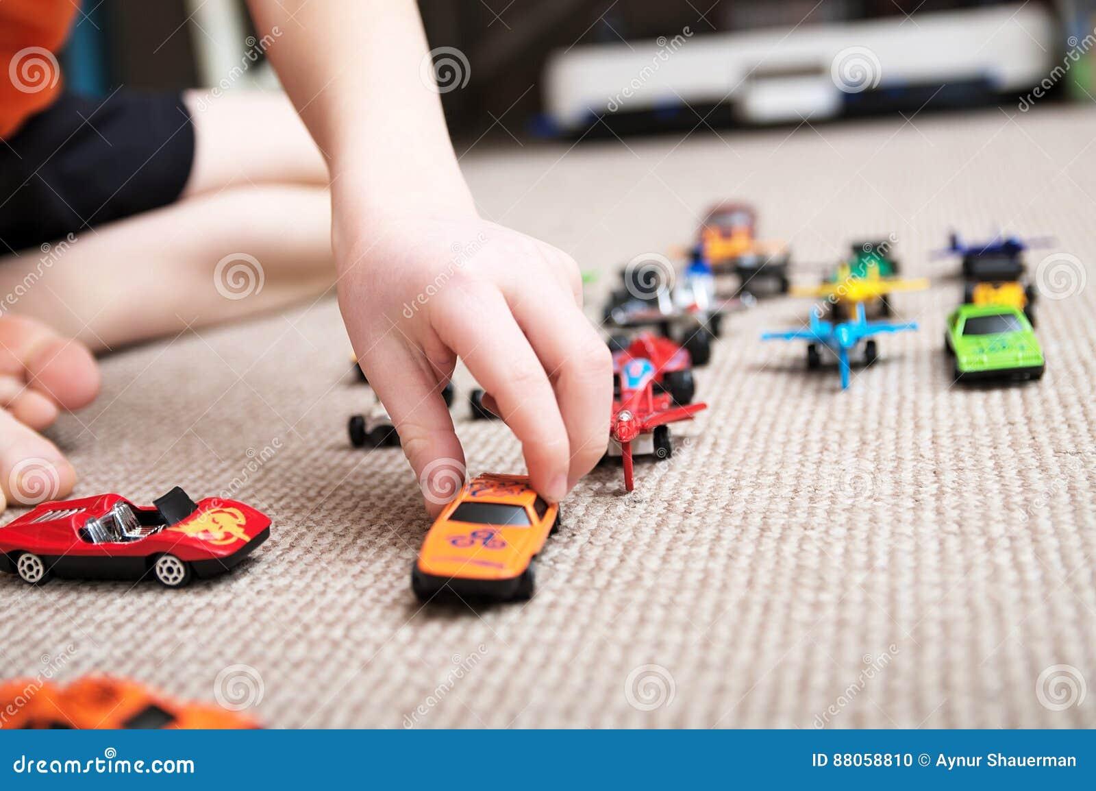 Pojke som spelar med bilsamlingen på matta Barnhandlek Trans.-, flygplan-, nivå- och helikopterleksaker för barn