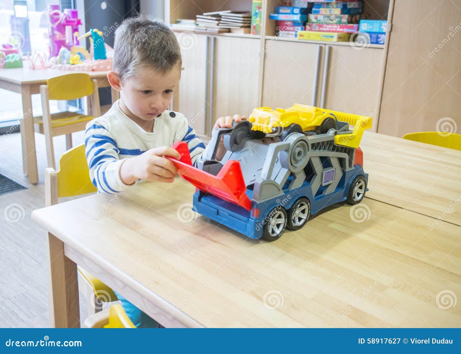 Pojke som spelar med leksaker i dagis