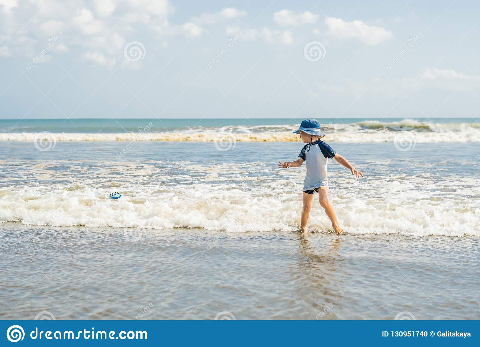 Pojke som spelar på stranden i vattnet