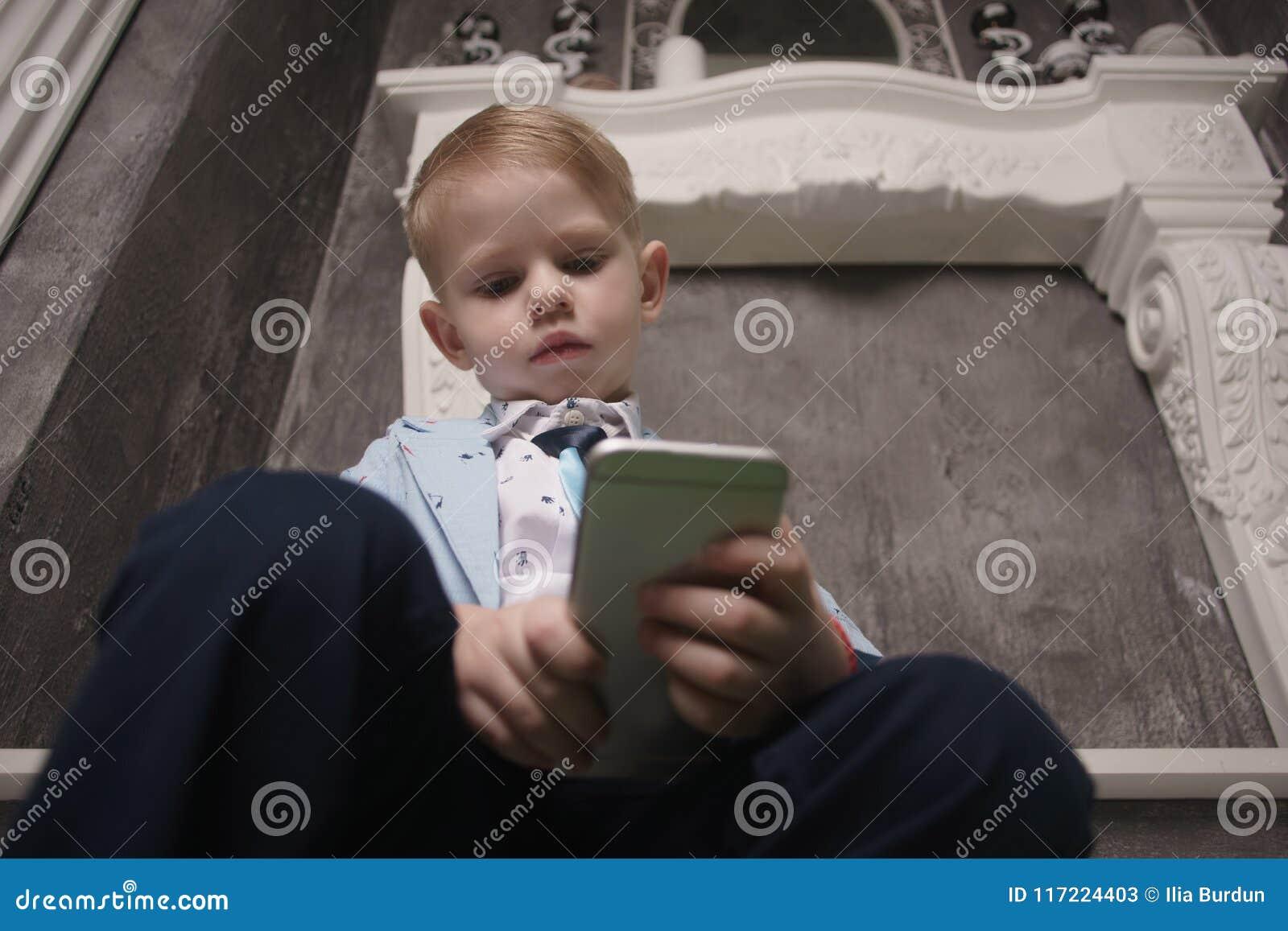 Pojke som spelar smartphonen på säng Hållande ögonen på smartphone ungebrukstelefon och leklek barnbruksmobil hemfallen lek och