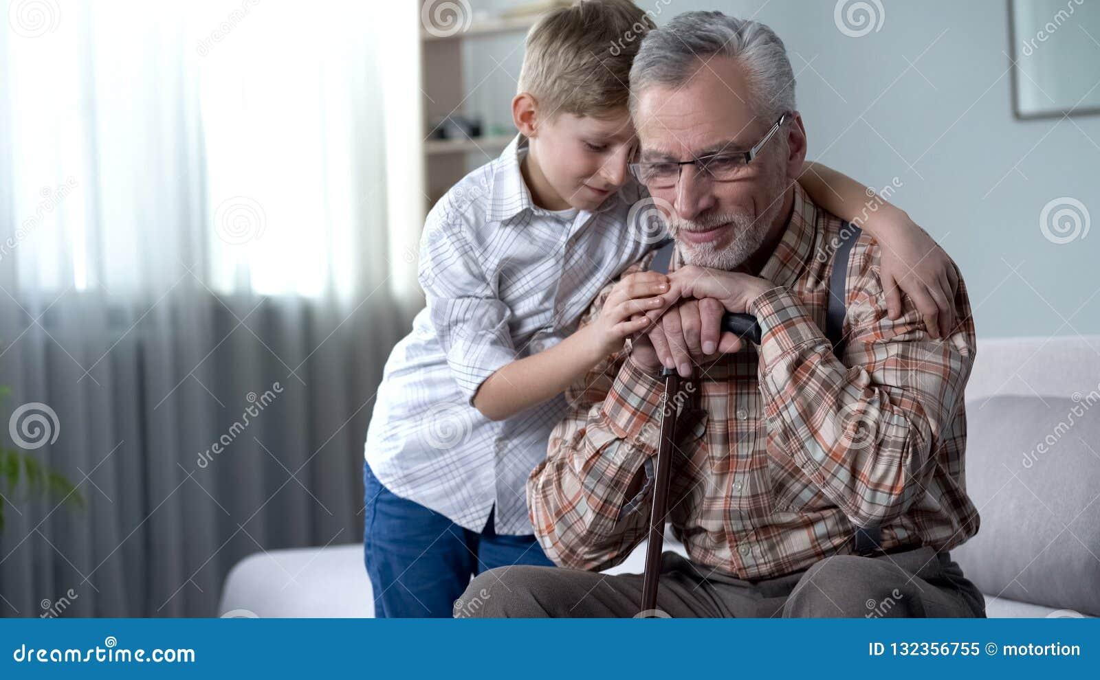 Pojke som tröstar den gamla ensamma mannen som omfamnar honom, välgörenhetprogram i vårdhem