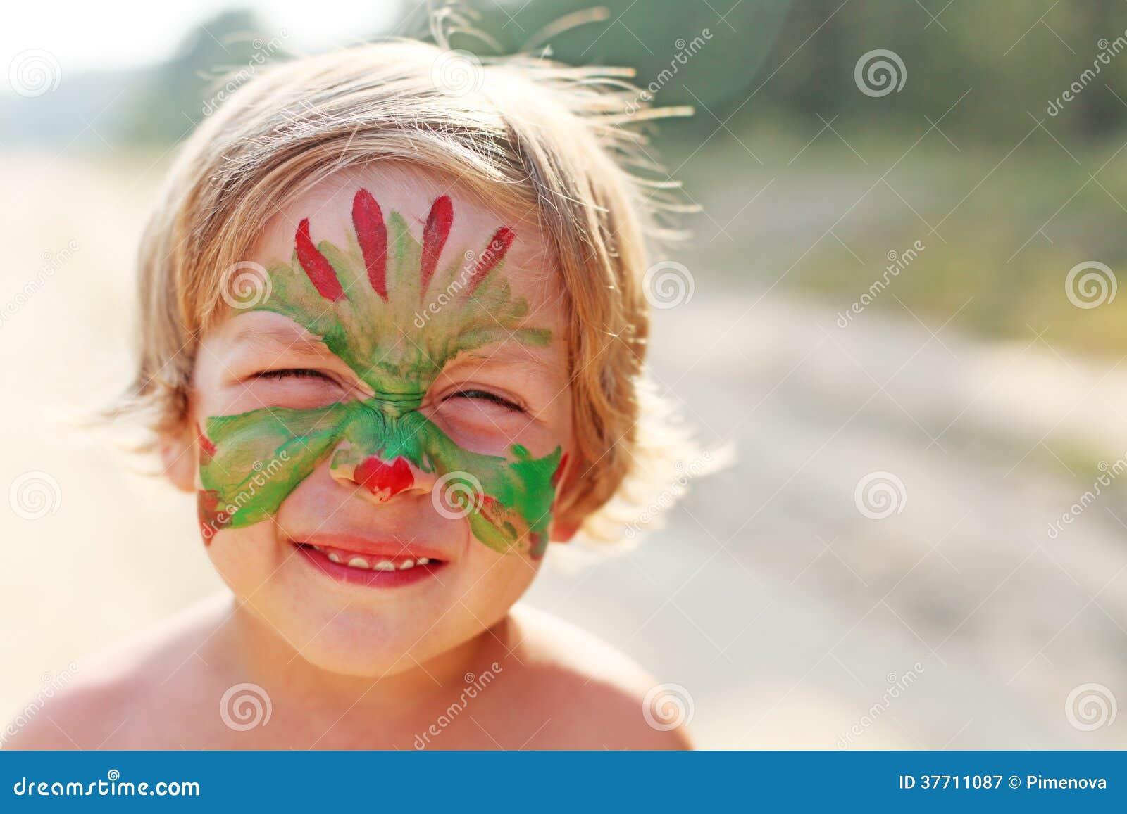 Pojkebarn med en maskering på hennes framsida