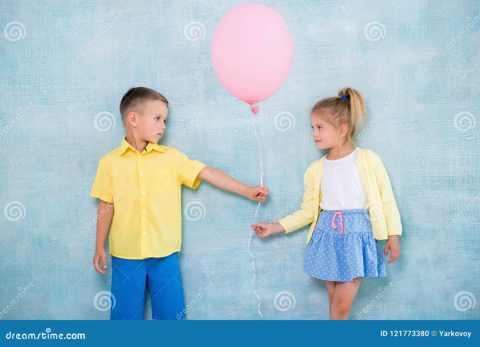 Pojkebarnet ger en ballong till en flicka Tecken av uppmärksamhet, sympati och kurtis