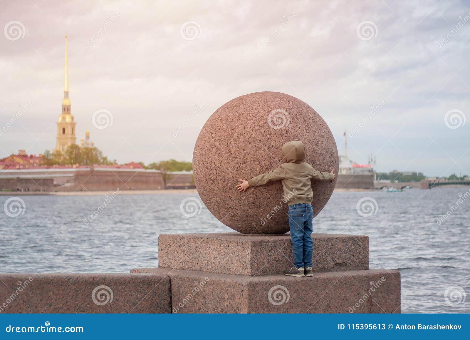 Pojkeförsök att krama den enorma stenbollen i St Petersburg
