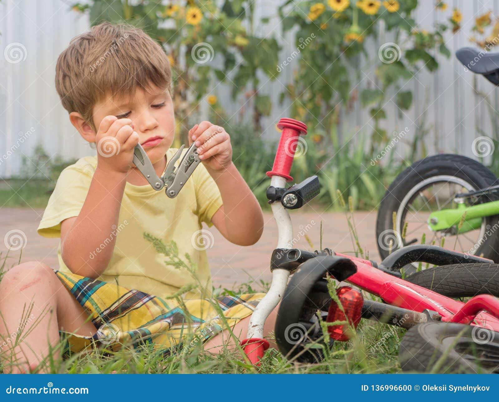 Pojkefixandecykel Framdel bakgårdbakgrund Transport och barn Cirkulering på gräset lyckligt barndombegrepp