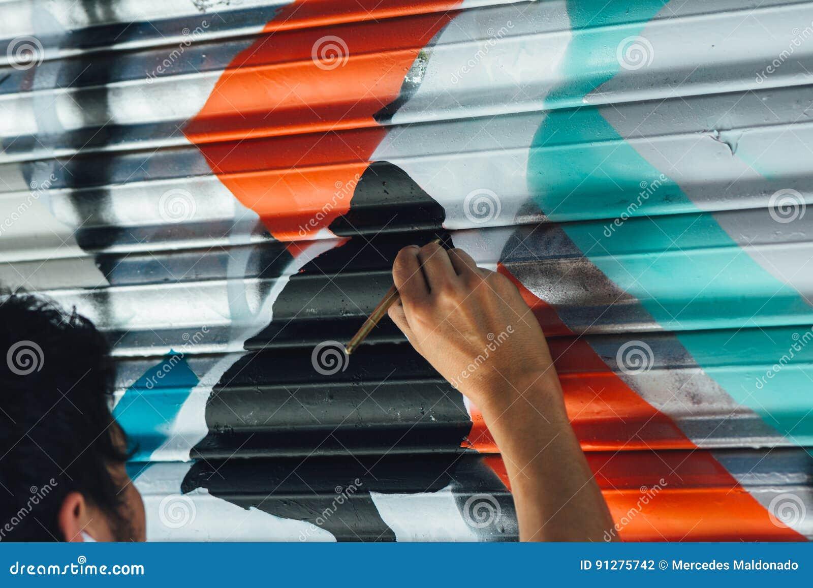 Pojkegrafitti som målas med borsten, på rullgardinen av ett lager