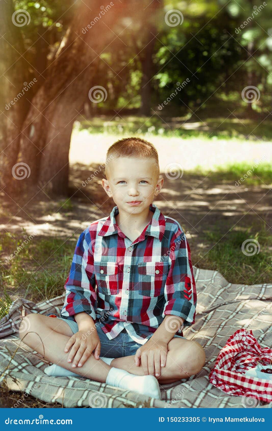 Pojken äter bäret på sommarpicknick
