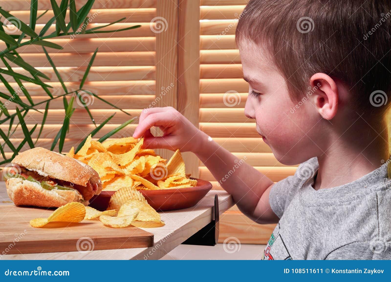 Pojken äter läckra potatischiper i kafé Barnet rymmer chiperna i hans hand På tabelllögnerna biten varmkorv Skjutit i en studio