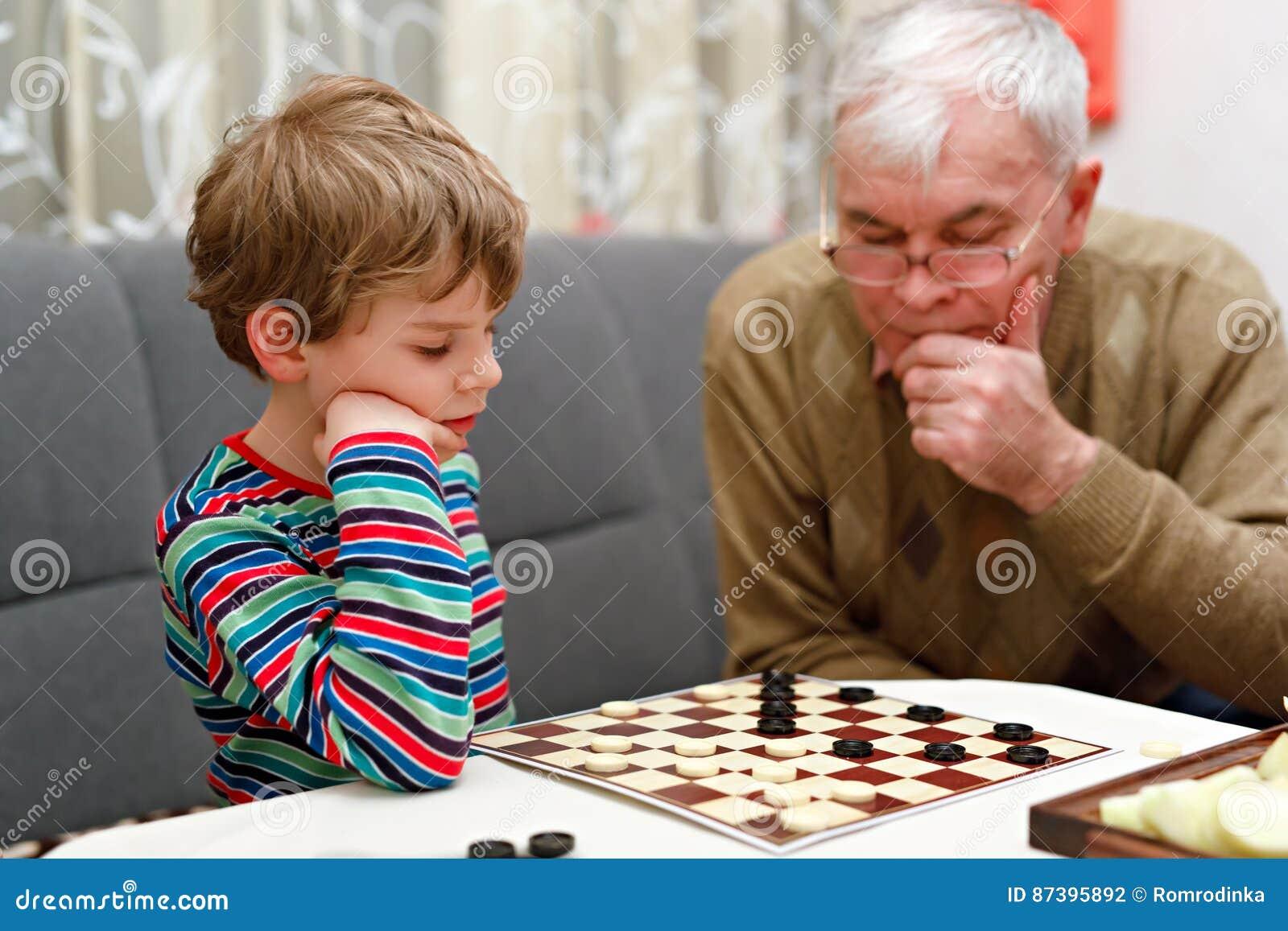 Pojken för den lilla ungen och pensionärfarfadern som tillsammans spelar kontrollörer, spelar