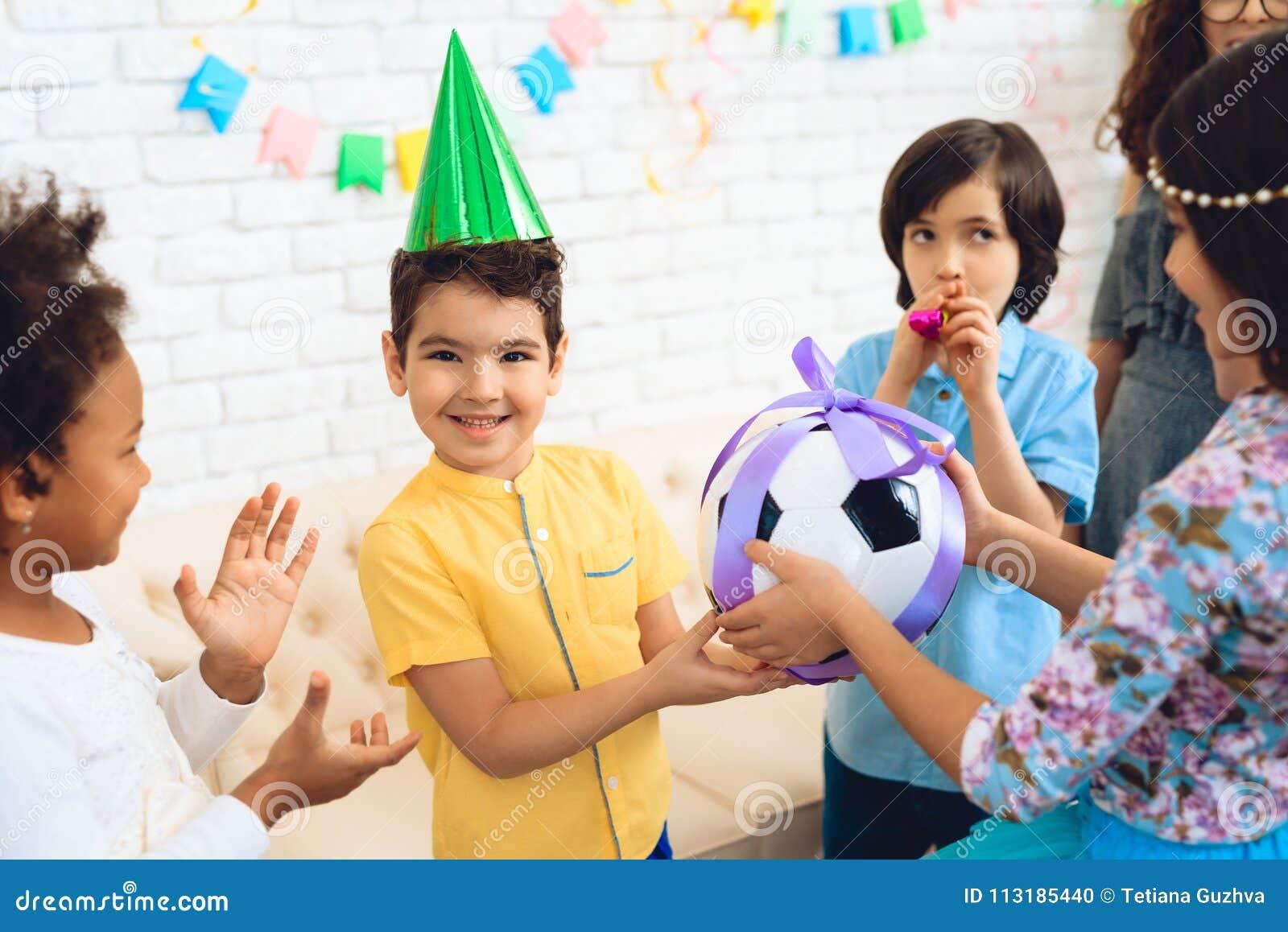 Pojken för den lyckliga födelsedagen mottar fotbollbollen som födelsedaggåvan lycklig deltagare för födelsedag