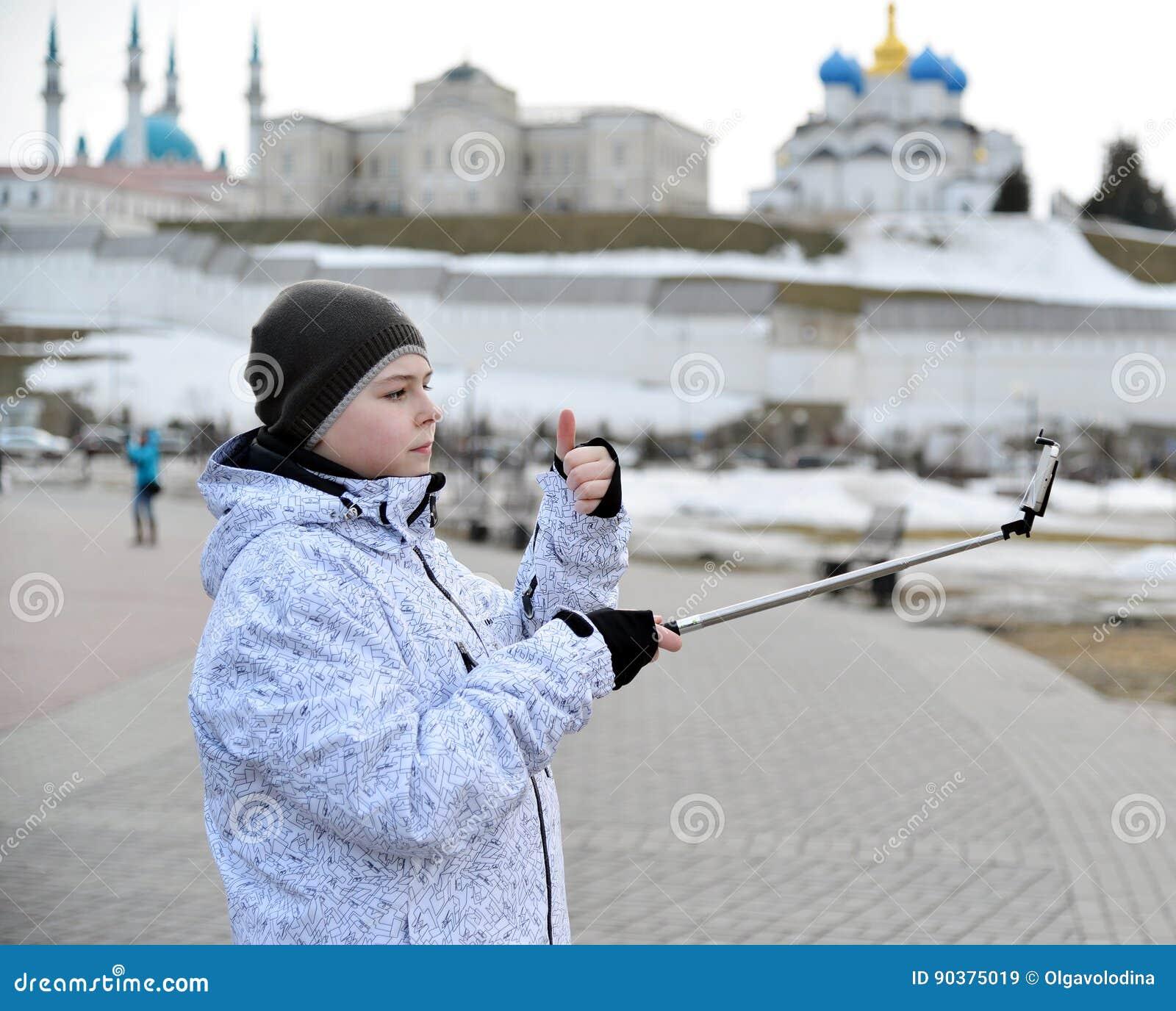 Pojken gör selfie på telefonen med självhäftande mot bakgrunden av den Kazan Kreml, Ryssland
