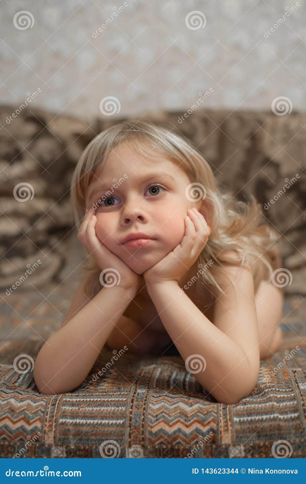 Pojken 4 gamla år hemma ligger på soffan och den hållande ögonen på TV:N blond pojkestående
