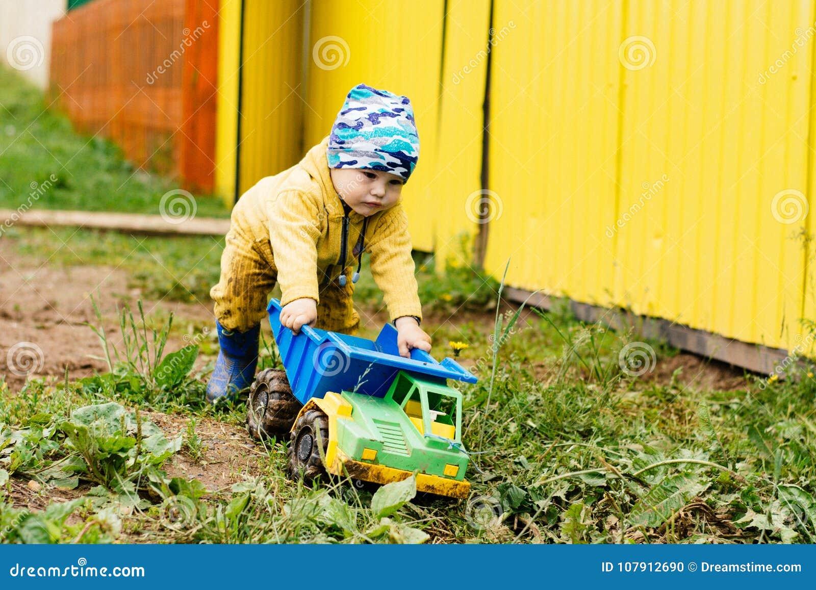 Pojken i den gula dräkten som spelar med en leksakbil i smutsen