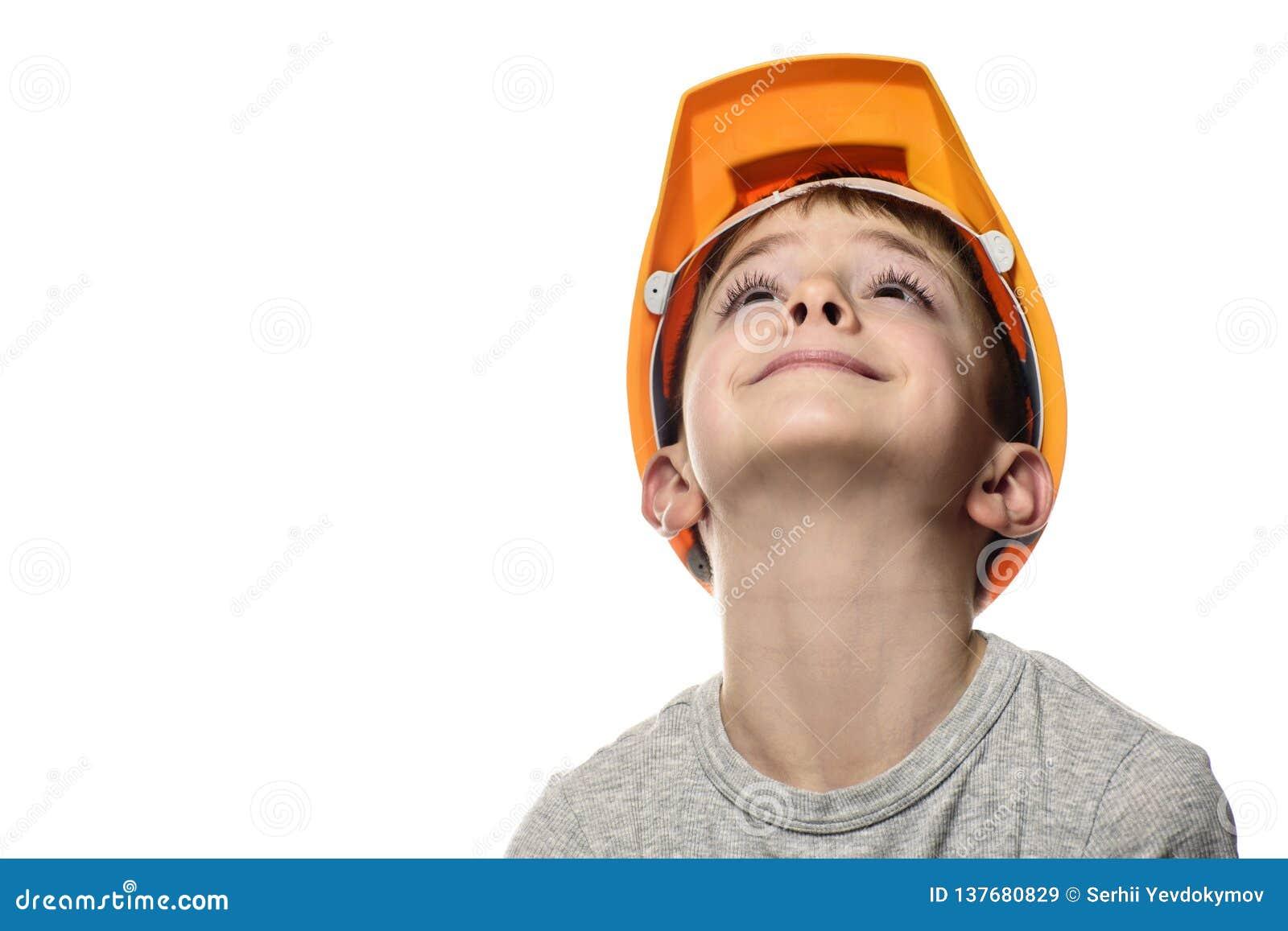 Pojken i den orange konstruktionshjälmen lyftte upp hans huvud Stående framsida Isolat på vitbakgrund