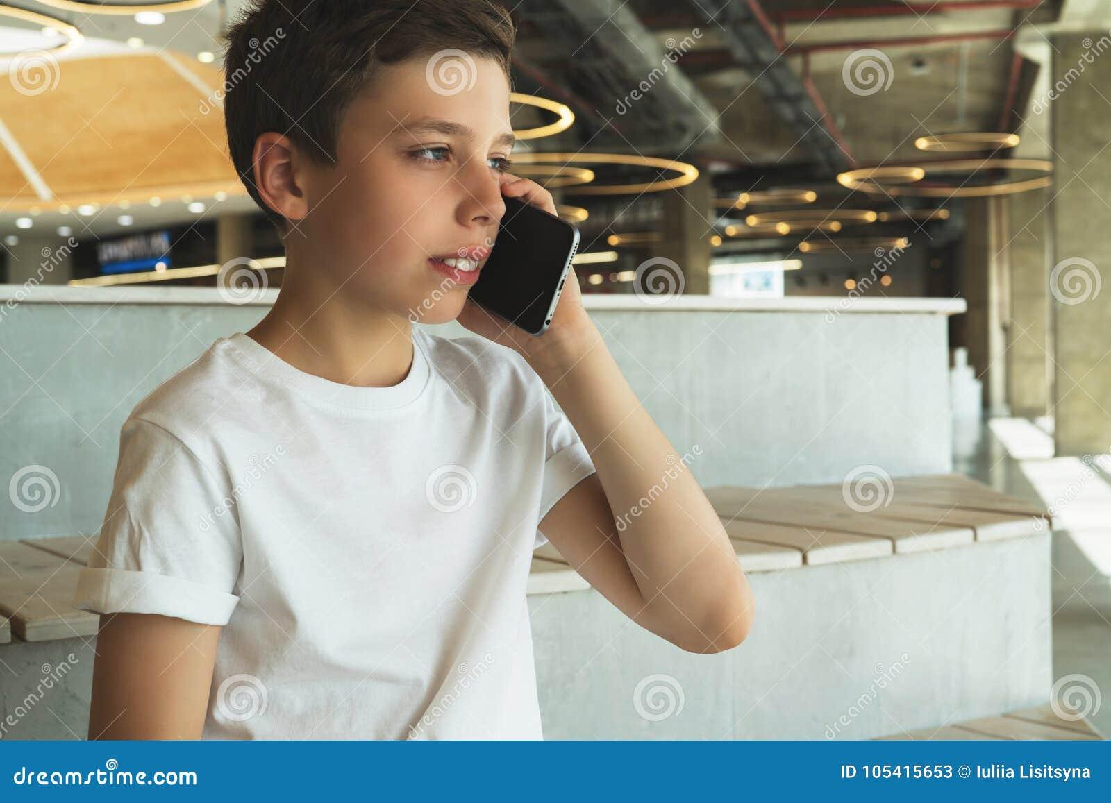 Pojken i den vita t-skjortan sitter inomhus och talar på hans mobiltelefon En tonåring använder en mobiltelefon och att kalla som