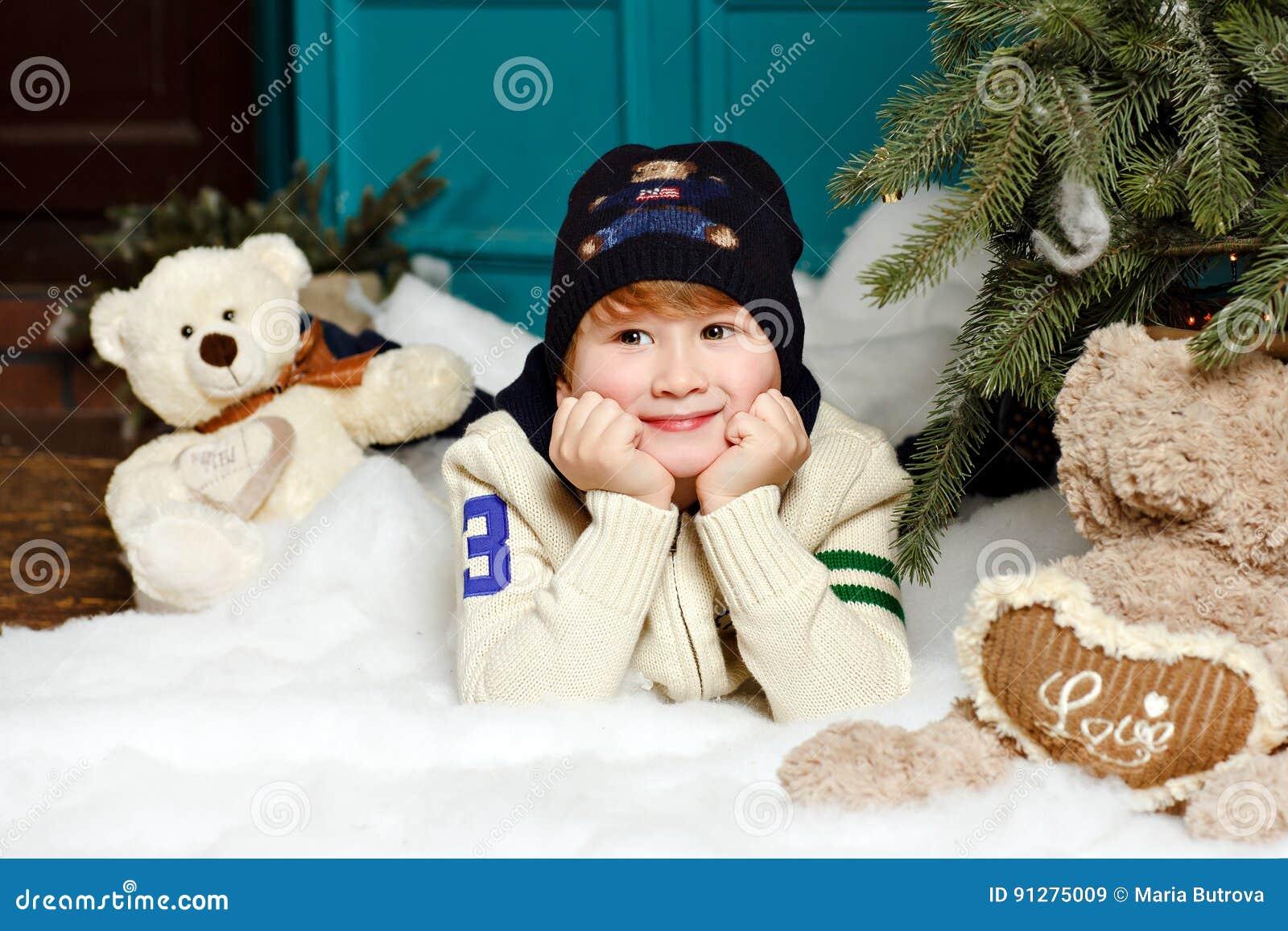 Pojken i hatt ler och ligger på den insnöade julen för en studio