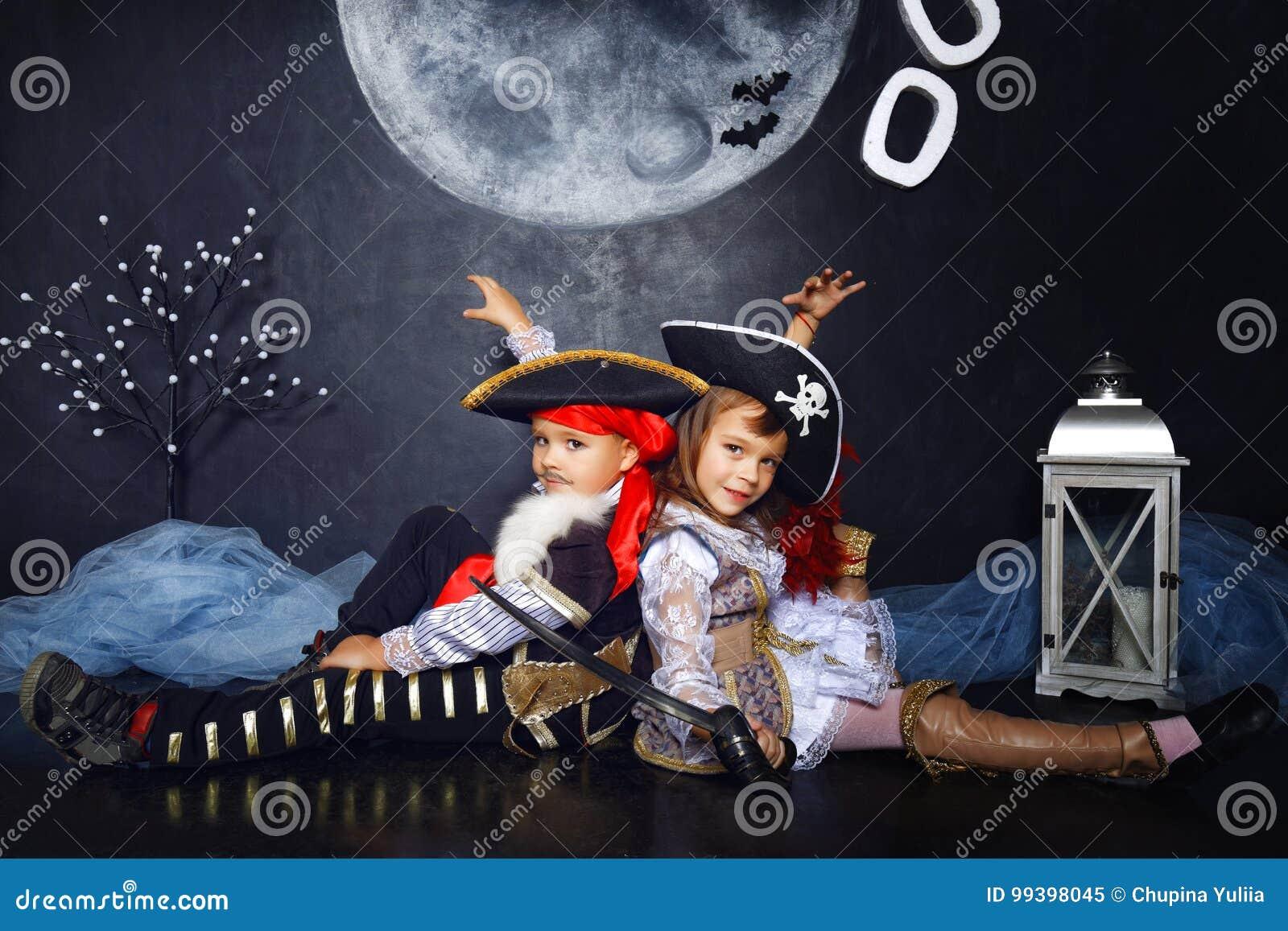 Pojken och flickan piratkopierar in dräkter för den grymma säger miniatyrreaperen halloween för kalenderbegreppsdatumet lyckliga
