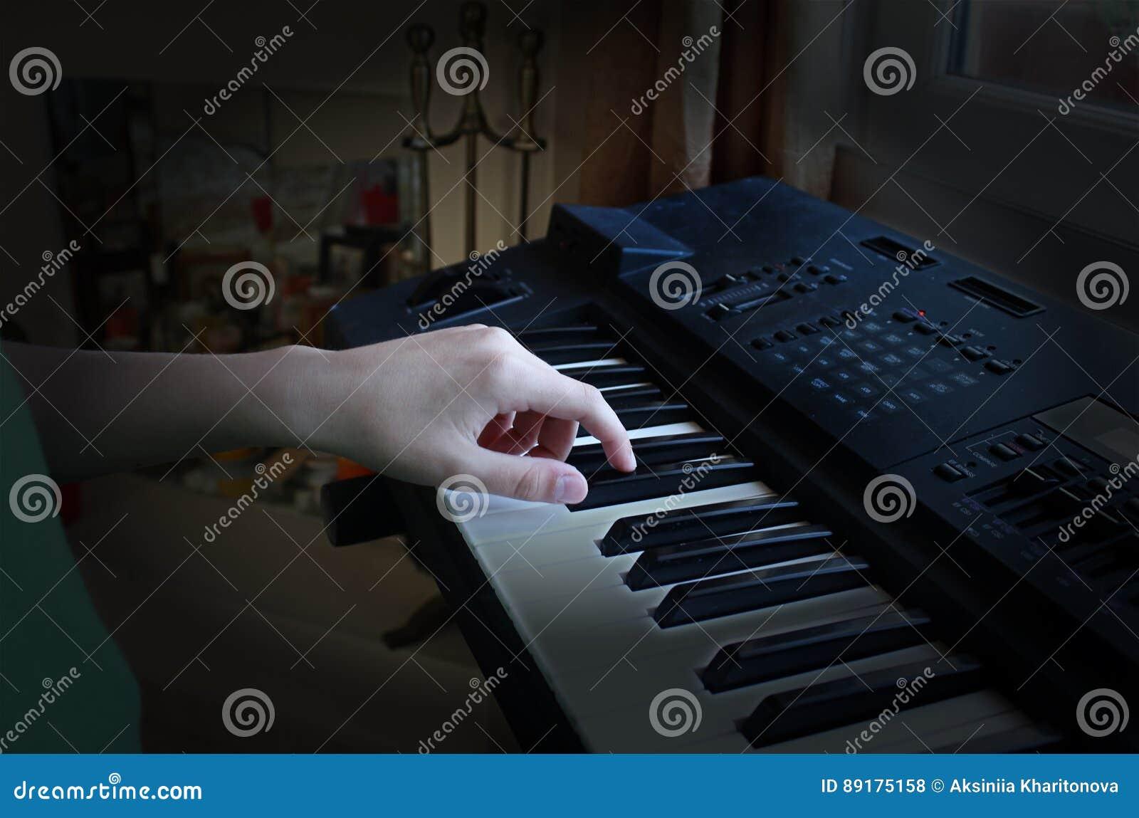 Pojken spelar det elektroniska pianot