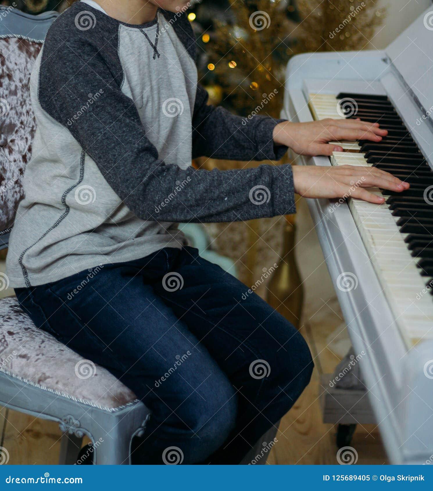 Pojken spelar pianot Han sitter på en stol nära pianoforten Övning spela instrumentet trycker på pianotangenterna