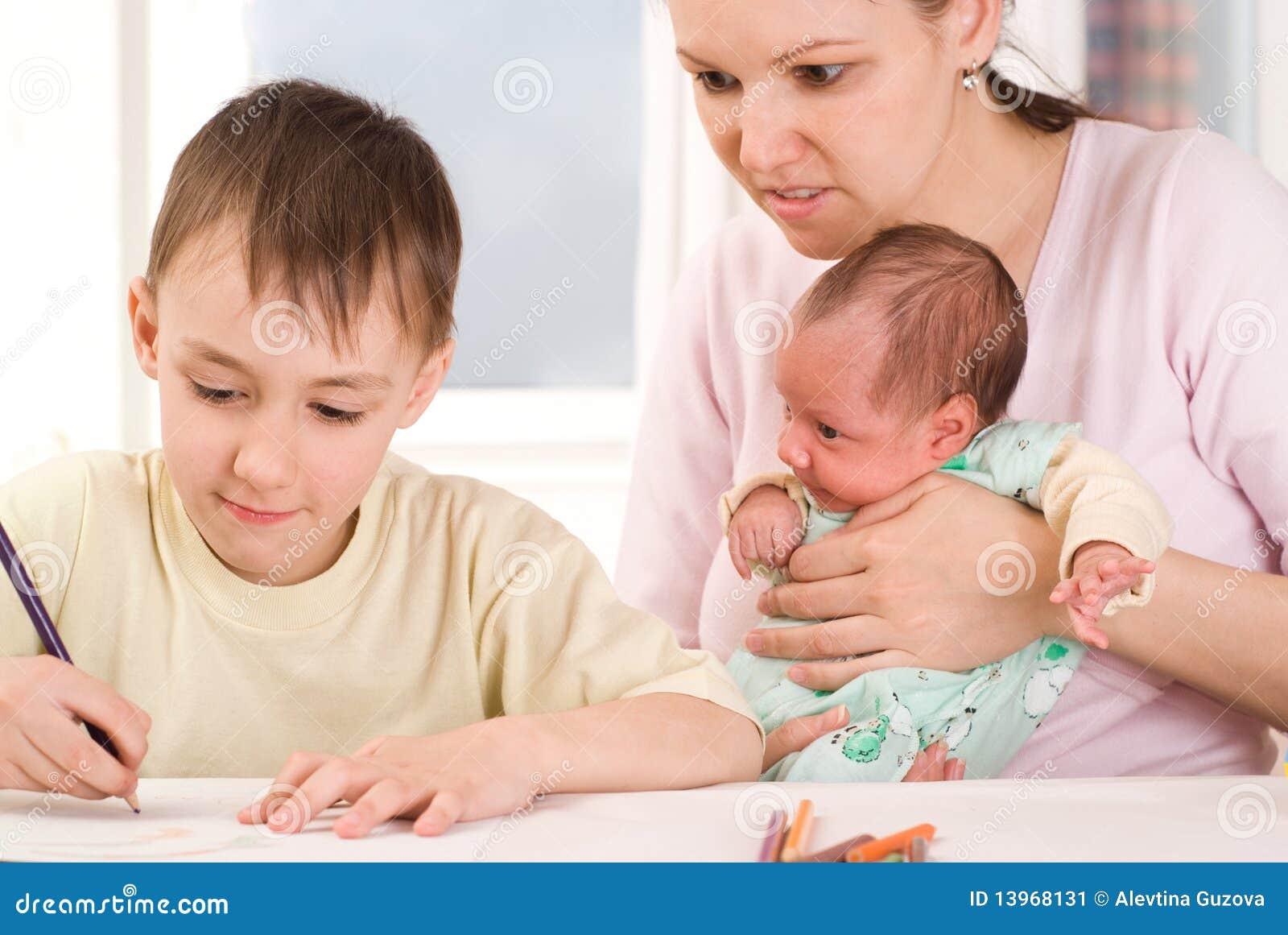 Pojken tecknar med hans moder och nyfött