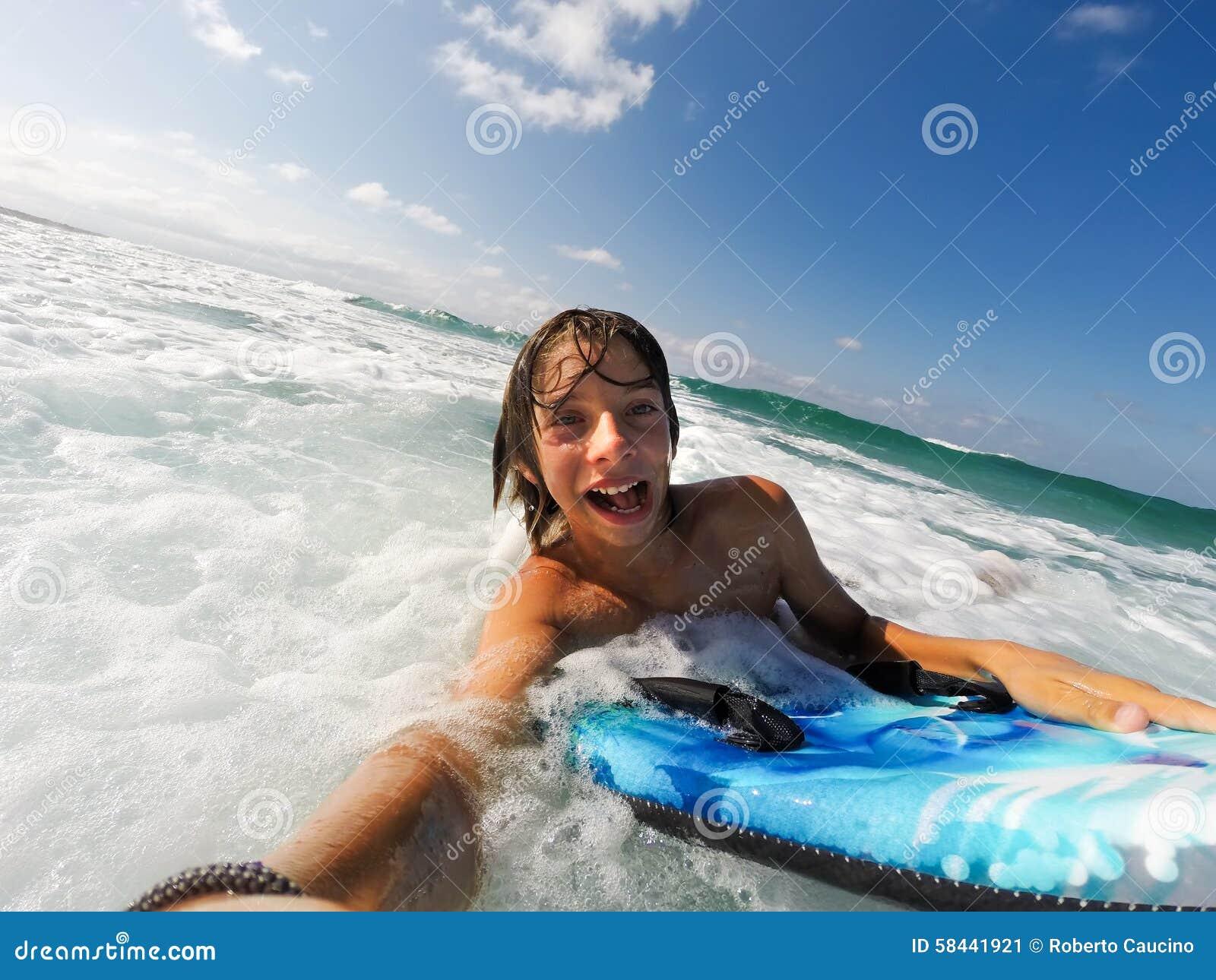 Pojken tycker om att rida vågorna med en surfingbräda