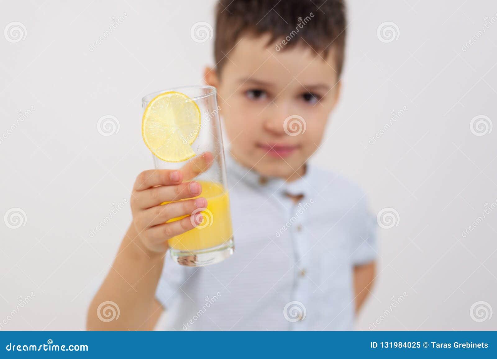 Pojken visar ett exponeringsglas med lemonad
