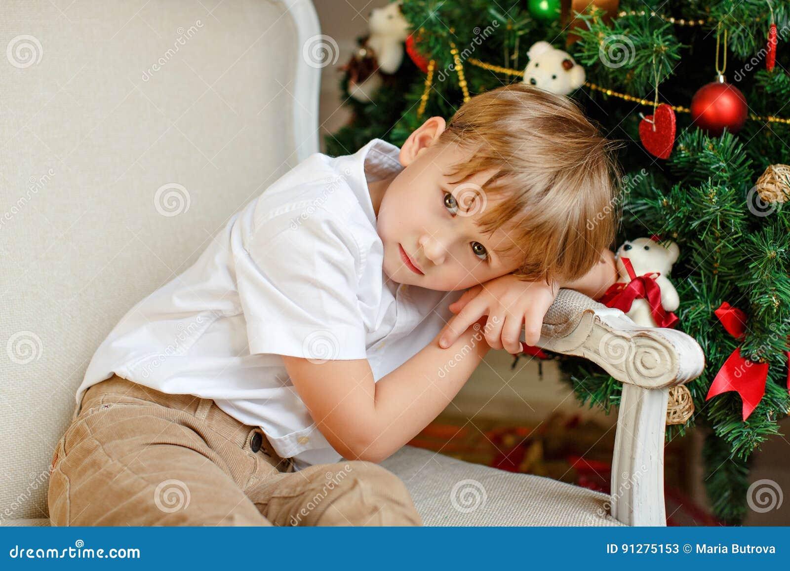 Pojkesammanträde i en stol och ledset på jul