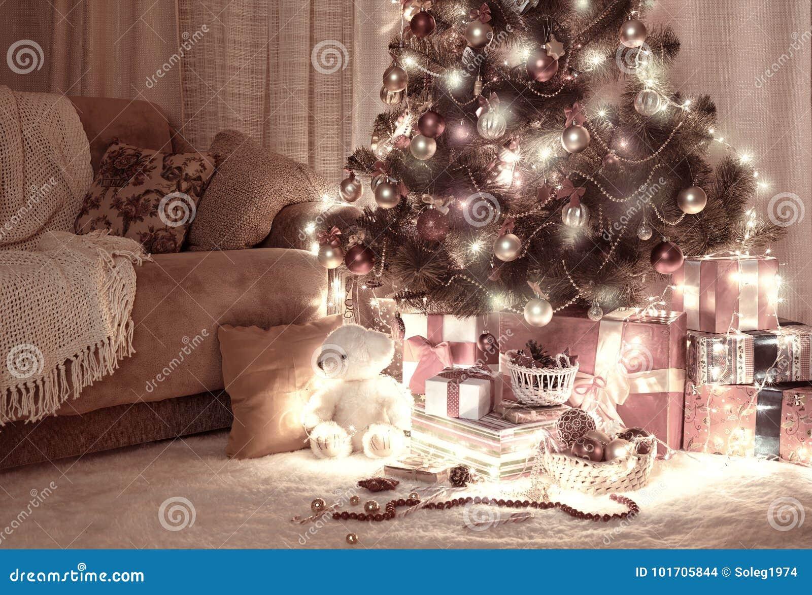 Pokój w zmroku z iluminującą choinką, dekoracja i prezenty, domowy wnętrze przy nocą, czerwony brąz tonujący