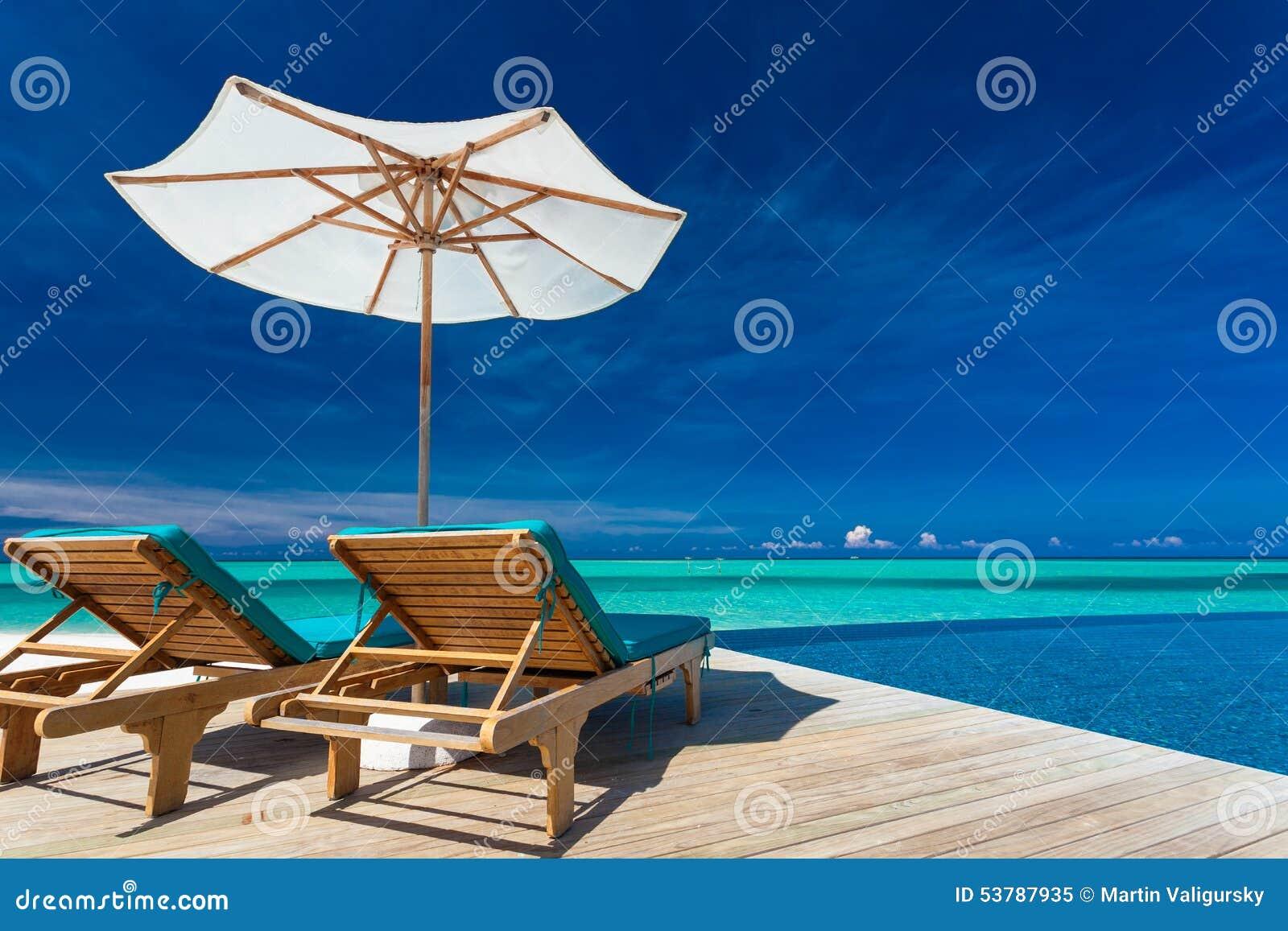 Pokładów krzesła przegapia nieskończoność basenu i tropikalnej laguny