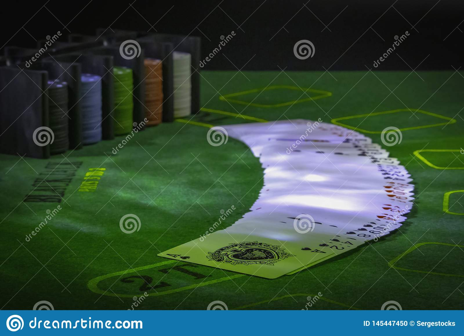 Pokład karty do gry i kasyno szczerbi się na zielonym stole dla Blackjack zaświecającego z partyjnymi światłami