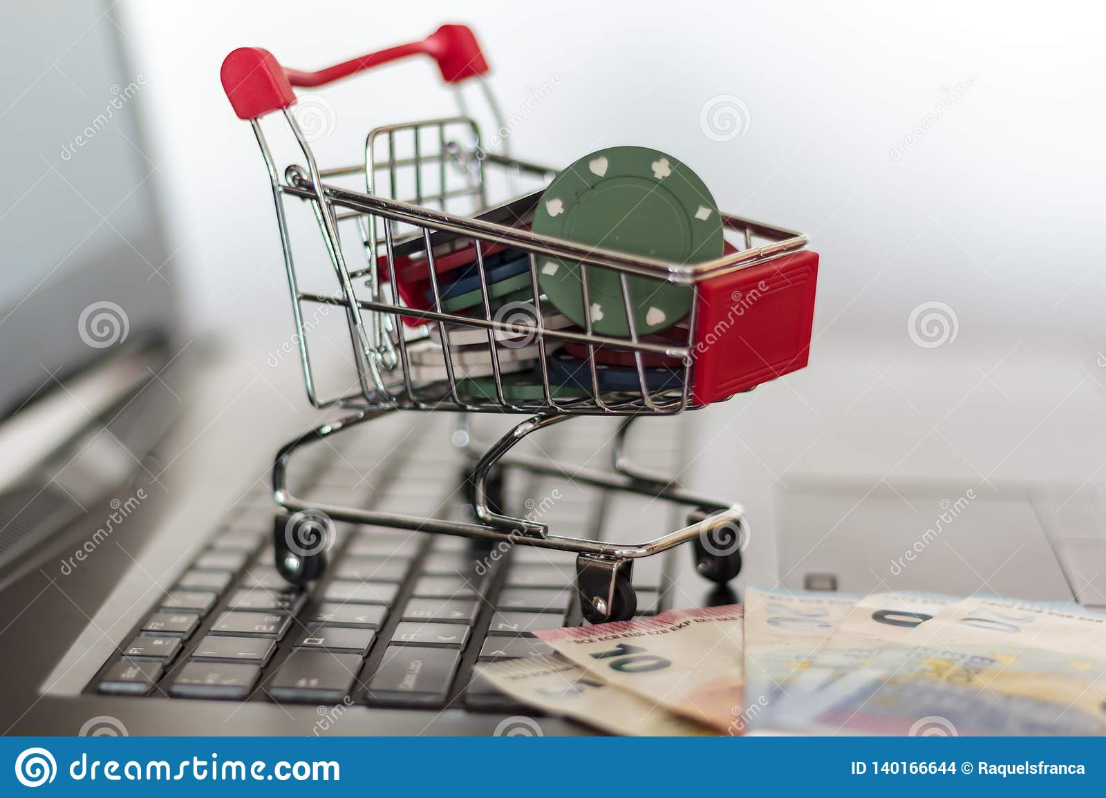 Poker chips in a trolley and euro banknotes on a computer. Online Gambling addiction concept