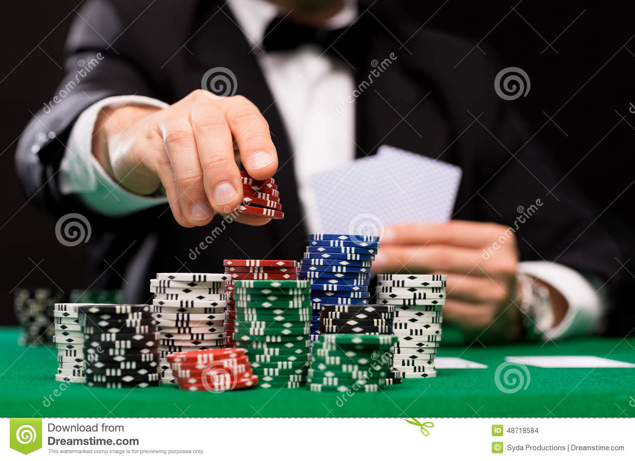 Poker player with cards and chips at casino