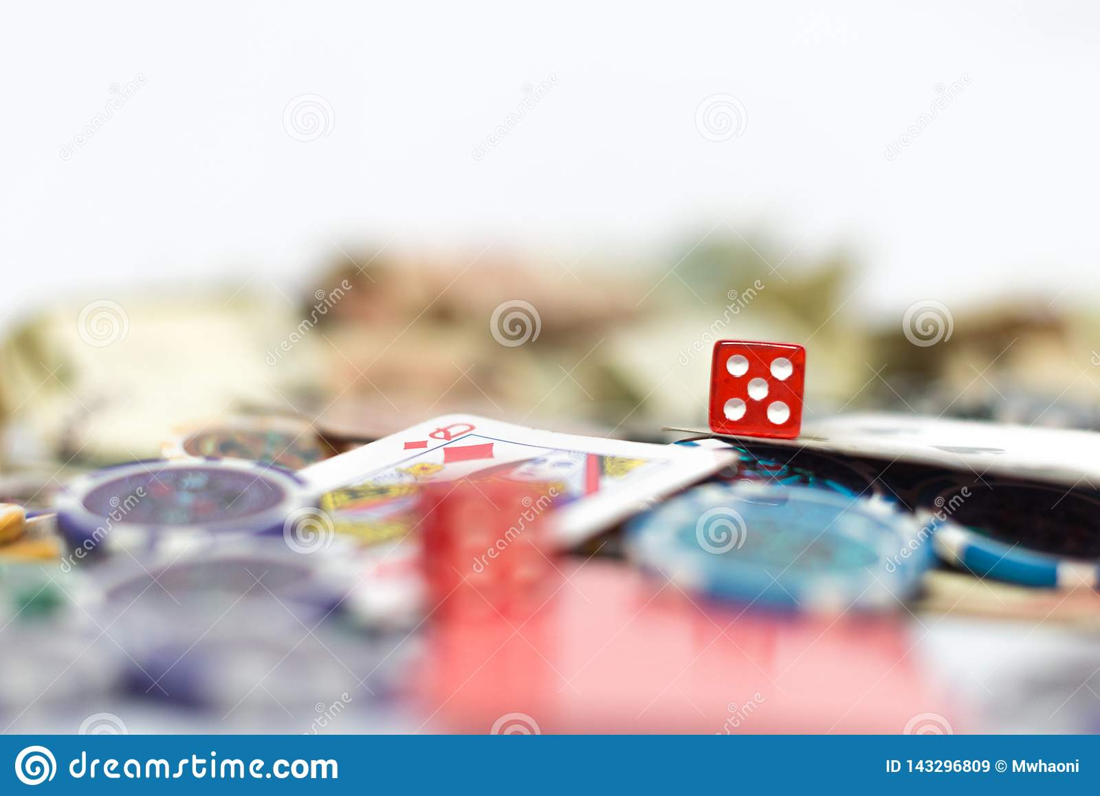Poker table with cards, dice, poker chips and money in background