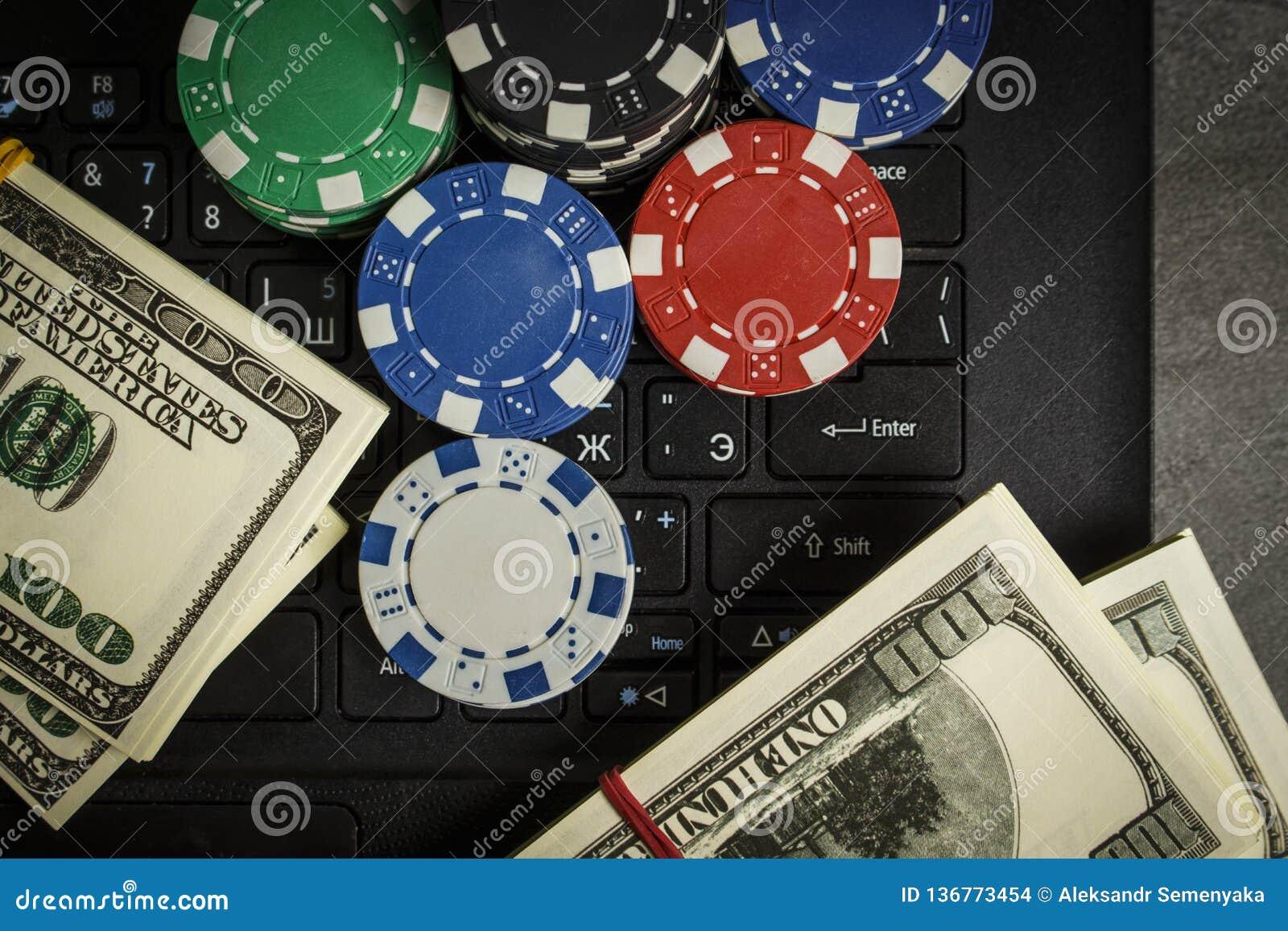 Pokerchiper och packar av dollar på en bärbar dator