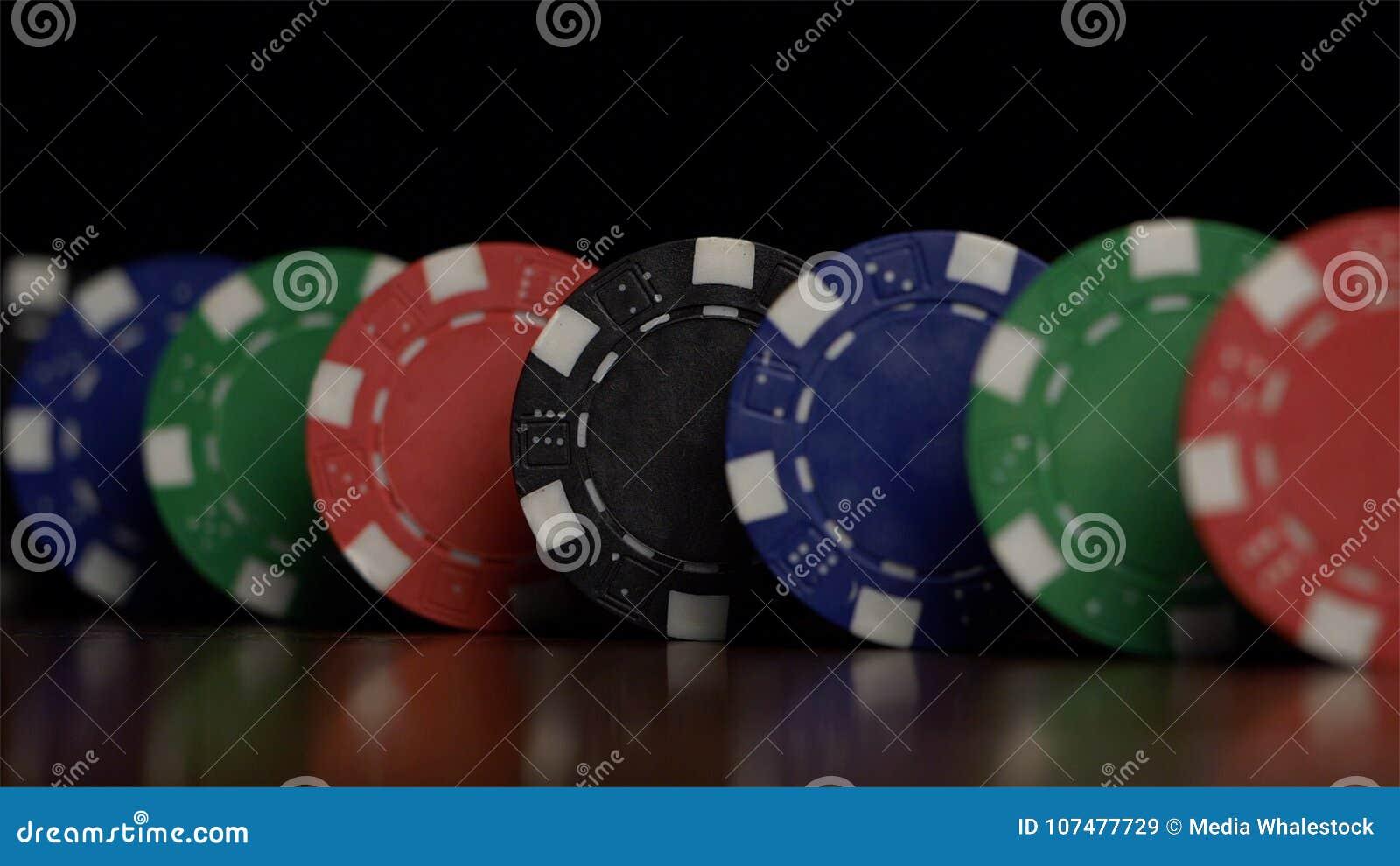 Pokerchips stehen in Folge auf einem schwarzen Hintergrund, ein Domino-Effekt Spielend sind Pokerchips auf dem Tisch, ein Symbol