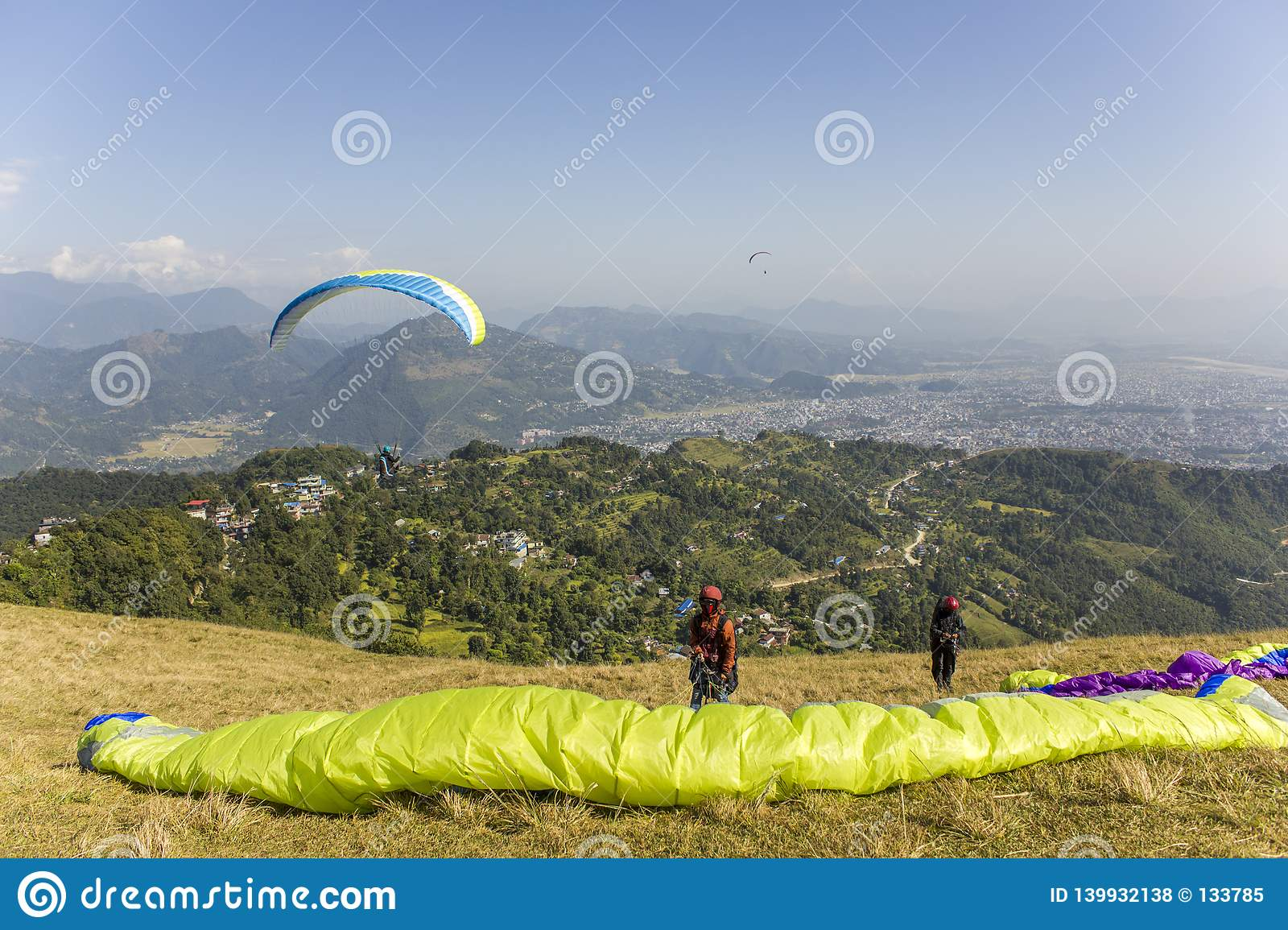 Two paragliders on the hillside before taking off against the backdrop of a mountain valley and flying