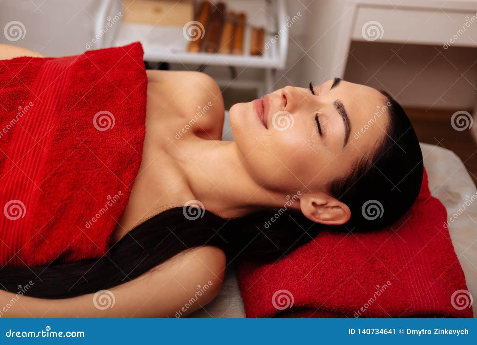 Pokojowy ciemnowłosy atrakcyjny kobiety lying on the beach na masażu łóżku