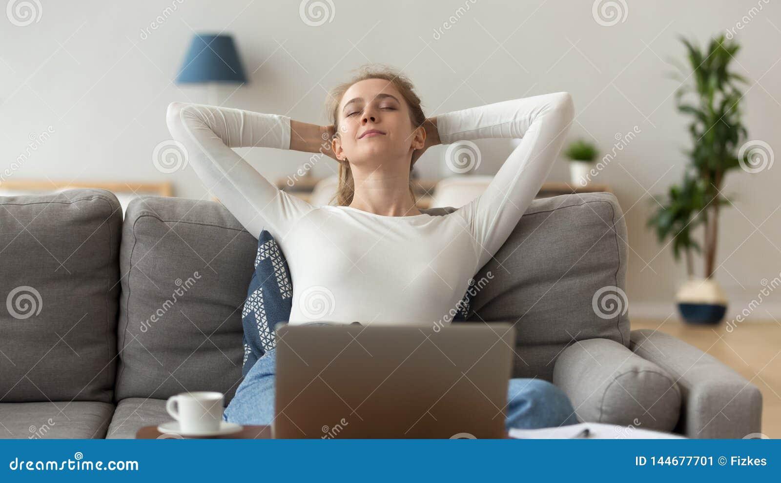 Pokojowy kobiety rozciąganie po koniec komputerowej pracy na wygodnej kanapie