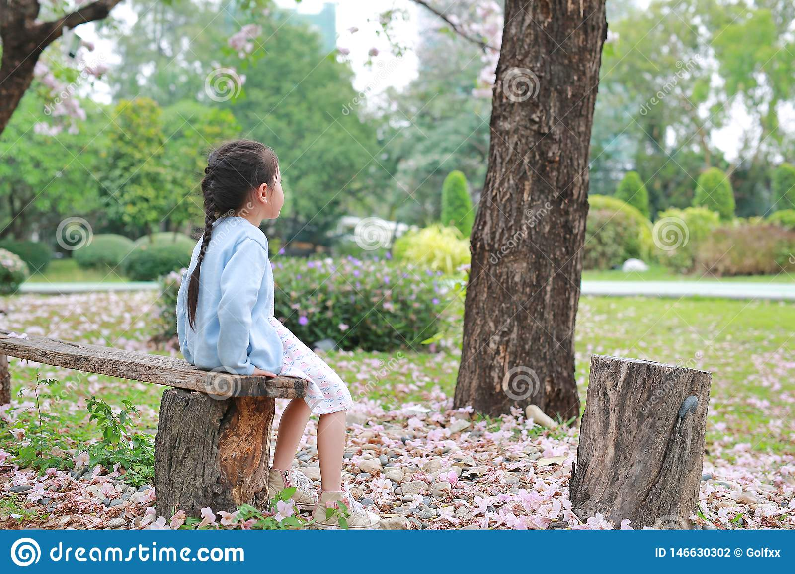 Pokojowy ma?ej dziewczynki obsiadanie na drewnianej nazwie u?ytkownikiej lato ogr?d z przygl?daj?cym za